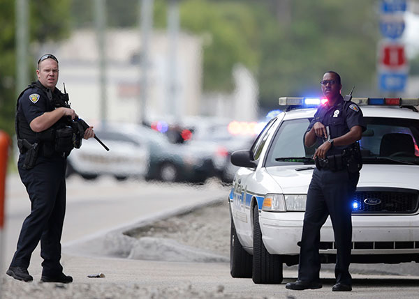 <div class='meta'><div class='origin-logo' data-origin='none'></div><span class='caption-text' data-credit='Lynne Sladky/AP Photo'>Police officers stand on the perimeter road along the Fort Lauderdale-Hollywood International Airport after a shooter opened fire inside a terminal of the airport.</span></div>
