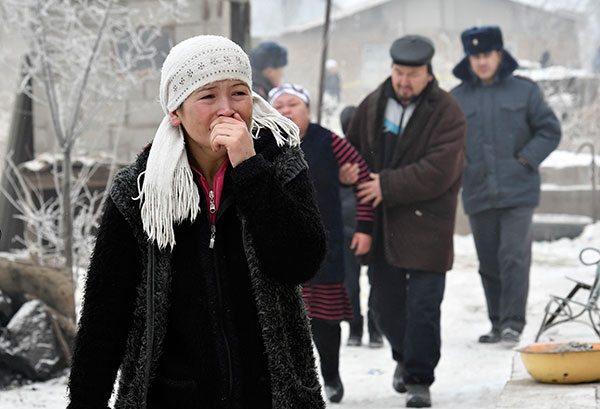 <div class='meta'><div class='origin-logo' data-origin='none'></div><span class='caption-text' data-credit='Vladimir Voronin/AP Photo'>Relatives of victims of a crashed plane watch as Kyrgyz Emergency Ministry officials work among remains of a cargo plane at a residential area outside Bishkek, Kyrgyzstan.</span></div>
