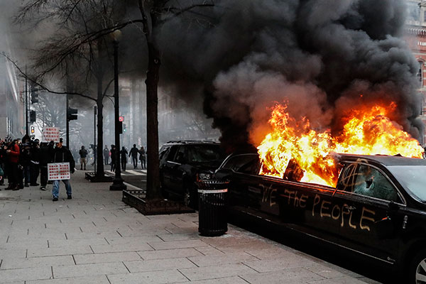 <div class='meta'><div class='origin-logo' data-origin='none'></div><span class='caption-text' data-credit='John Minchillo//AP Photo'>A parked limousine burns during a demonstration after the inauguration of President Donald Trump, Friday, Jan. 20, 2017.</span></div>