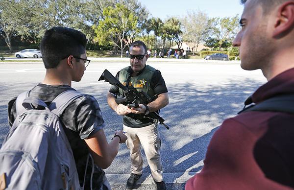 <div class='meta'><div class='origin-logo' data-origin='AP'></div><span class='caption-text' data-credit='AP Photo/Wilfredo Lee'>A law enforcement officer talks with students, Wednesday, Feb. 14, 2018, in Parkland, Fla.</span></div>
