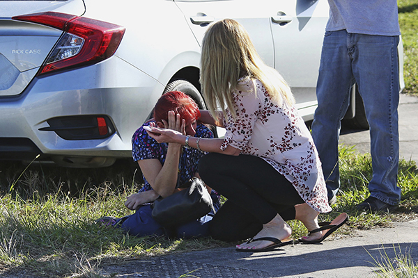 <div class='meta'><div class='origin-logo' data-origin='AP'></div><span class='caption-text' data-credit='AP Photo/Joel Auerbach'>A woman consoles another as parents wait for news regarding a shooting at Marjory Stoneman Douglas High School in Parkland, Fla., Wednesday, Feb. 14, 2018.</span></div>