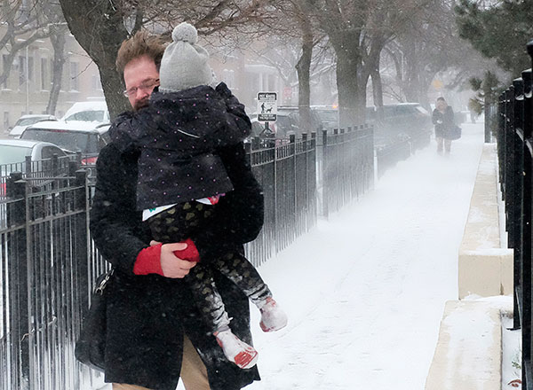 <div class='meta'><div class='origin-logo' data-origin='none'></div><span class='caption-text' data-credit='Kiichiro Sato/AP Photo'>A commuter fights wind gusts as he carries his daughter to school, Tuesday, March 14, 2017, in Chicago.</span></div>