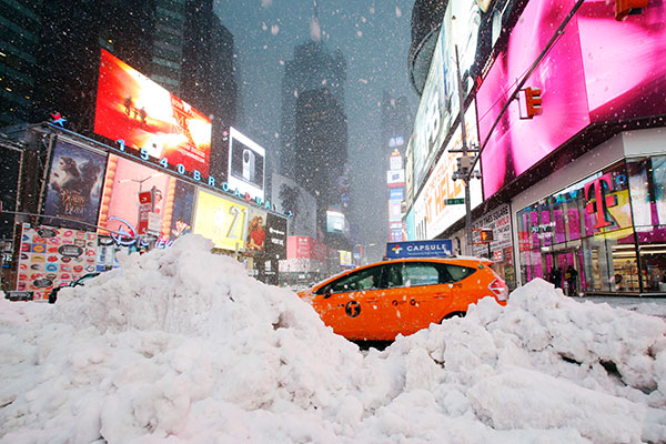 <div class='meta'><div class='origin-logo' data-origin='none'></div><span class='caption-text' data-credit='Mark Lennihan/AP Photo'>A taxi drives past piles of snow as a storm sweeps through Times Square, Tuesday, March 14, 2017, in New York.</span></div>