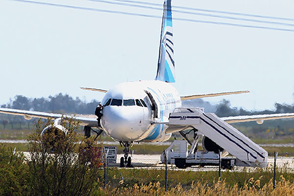 <div class='meta'><div class='origin-logo' data-origin='none'></div><span class='caption-text' data-credit='Petros Karadjias/AP Photo'>A man leaves the hijacked aircraft of Egyptair from the pilot's window after landing at Larnaca airport Tuesday, March 29, 2016.</span></div>