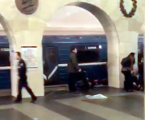 <div class='meta'><div class='origin-logo' data-origin='none'></div><span class='caption-text' data-credit='AP video via AP'>In this grab taken from AP video, Russian police officer, left, and people walk past the damaged train at the Tekhnologichesky Institut subway station in St.Petersburg, Russia.</span></div>