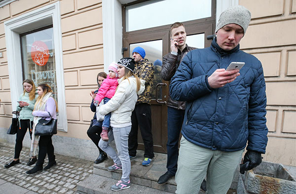 <div class='meta'><div class='origin-logo' data-origin='none'></div><span class='caption-text' data-credit='Peter KovalevTASS via Getty Images'>People use phones at the entrance to Tekhnologichesky Institut station of the St Petersburg metro in the aftermath of an explosion on Monday.</span></div>