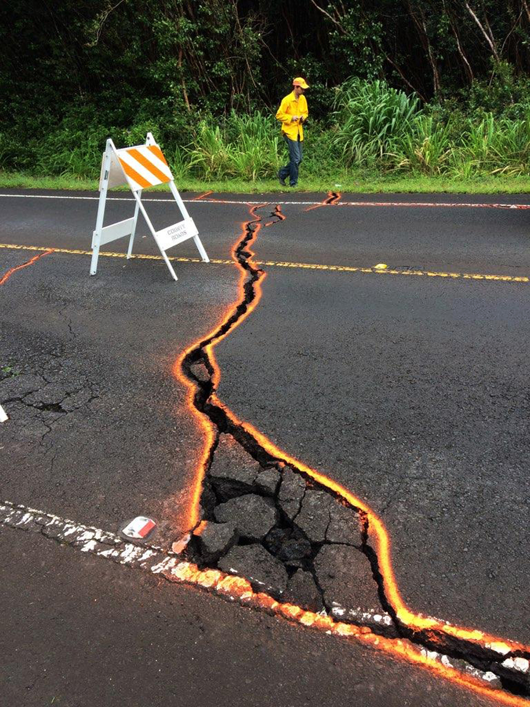 <div class='meta'><div class='origin-logo' data-origin='AP'></div><span class='caption-text' data-credit='USGS/AP'>This Monday, May 7, 2018, photo from the U.S. Geological Survey shows cracks in Highway 130, outlined on orange paint, in the Leilani Estates subdivision.</span></div>