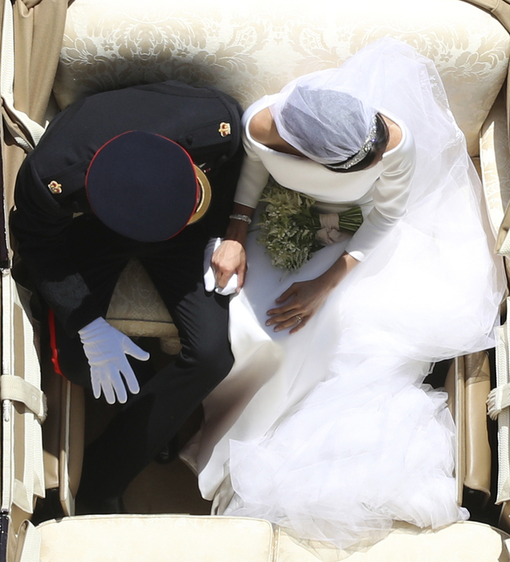 Britain's Prince Harry and Meghan Markle hold hands as they leave in a carriage after their wedding ceremony at St. George's Chapel in Windsor Castle