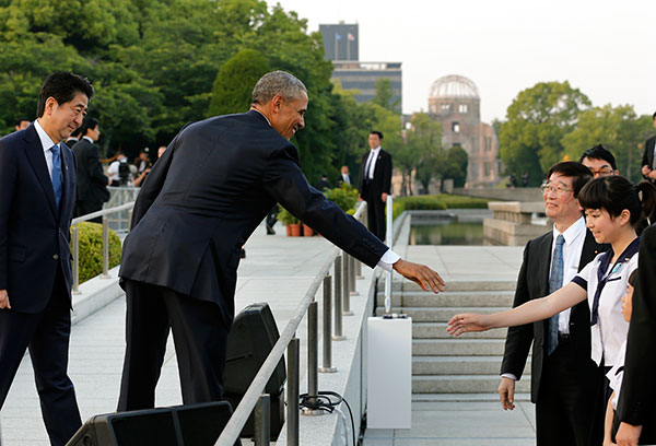 "<div class=""meta image-caption""><div class=""origin-logo origin-image none""><span>none</span></div><span class=""caption-text"">U.S. President Barack Obama reaches out to shake hands with a student after laying a wreath and giving a speech. (Kimimasa Mayama/Pool Photo via AP)</span></div>"