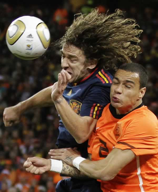 Spain&#39;s Carles Puyol, left, competes for the ball with Netherlands&#39; Gregory van der Wiel, right, during the World Cup final soccer match between the Netherlands and Spain. <span class=meta>(AP Photo&#47;Luca Bruno)</span>