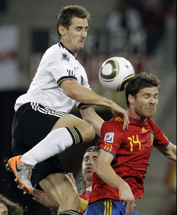 Germany&#39;s Miroslav Klose, left, outjumps Spain&#39;s Xabi Alonso, right, during the World Cup semifinal soccer match between Germany and Spain at the stadium in Durban, South Africa. <span class=meta>(AP Photo&#47;Gero Breloer)</span>