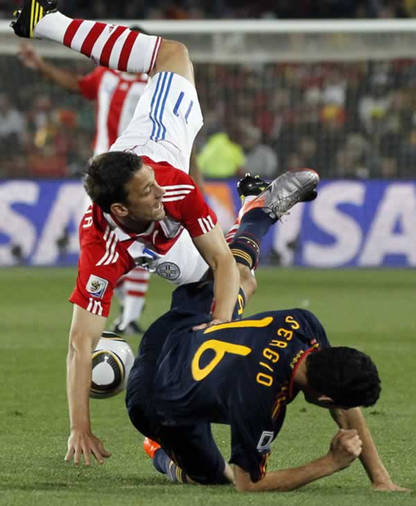 Paraguay&#39;s Jonathan Santana, left, is airborne after a challenge with Spain&#39;s Sergio Busquets during the World Cup quarterfinal soccer match between Paraguay and Spain. <span class=meta>(AP Photo&#47;Bernat Armague)</span>