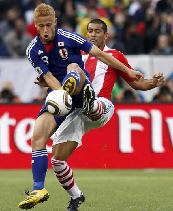 Paraguay&#39;s Paulo Da Silva, right, tackles Japan&#39;s Keisuke Honda, left, during the World Cup round of 16 soccer match between Paraguay and Japan. <span class=meta>(AP Photo&#47;Luca Bruno)</span>