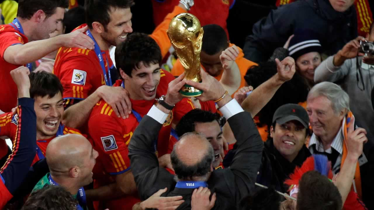 Spain head coach Vicente Del Bosque, bottom center, holds up the World Cup trophy at the end of the World Cup final soccer match between the Netherlands and Spain on July 11, 2010. <span class=meta>(AP Photo&#47;Michael Sohn)</span>