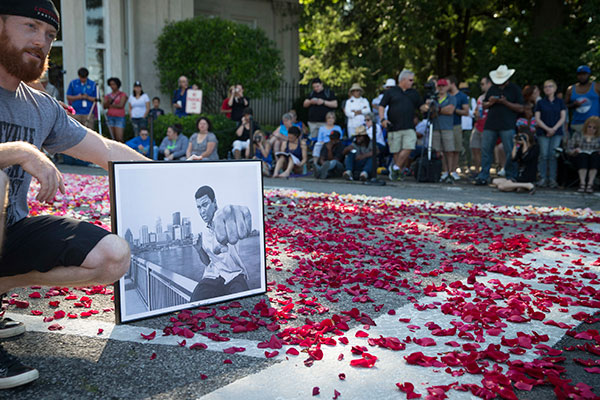 "<div class=""meta image-caption""><div class=""origin-logo origin-image none""><span>none</span></div><span class=""caption-text"">Nick Smith, of Louisville, poses for a photograph holding a drawing of Muhammad Ali as spectators wait for the arrival of Ali's funeral procession to enter Cave Hill Cemetery. (John Minchillo/AP Photo)</span></div>"
