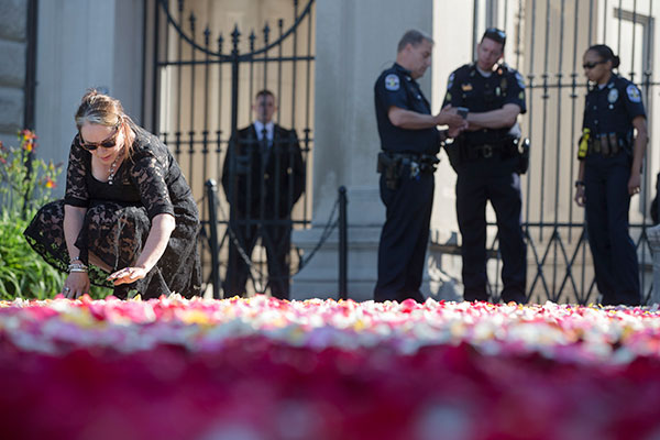 "<div class=""meta image-caption""><div class=""origin-logo origin-image none""><span>none</span></div><span class=""caption-text"">Maggie Cassaro, of Louisville, spreads roses along the entrance way to Cave Hill Cemetery as police stand guard before the arrival of Muhammad Ali's funeral procession. (John Minchillo/AP Photo)</span></div>"