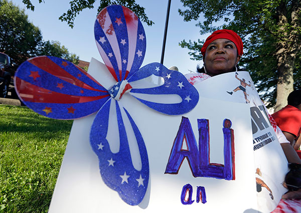 "<div class=""meta image-caption""><div class=""origin-logo origin-image none""><span>none</span></div><span class=""caption-text"">Frances Woods holds a sign saluting Muhammad Ali as she awaits his funeral procession to make its way down Muhammad Ali Boulevard in Louisville, Ky. Friday, June 10. (Michael Conroy/AP Photo)</span></div>"