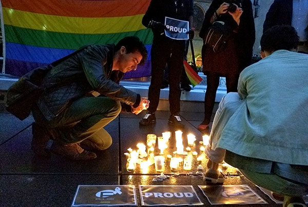 <div class='meta'><div class='origin-logo' data-origin='none'></div><span class='caption-text' data-credit='Raphael Satter/AP Photo'>A man lights a candle during a spontaneous vigil to remember those slain and wounded at an Orlando nightclub, Sunday June 12, 2016 in Paris.</span></div>