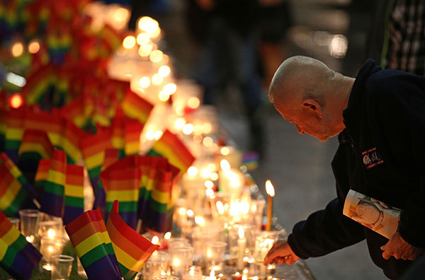 <div class='meta'><div class='origin-logo' data-origin='none'></div><span class='caption-text' data-credit='Rick Rycroft/AP Photo'>A man places a candle at an impromptu memorial set up in Sydney, Monday, June 13.</span></div>