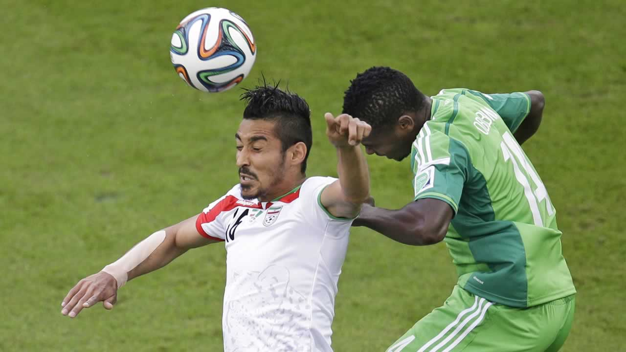 Iran&#39;s Reza Ghoochannejhad, left, and Nigeria&#39;s Godfrey Oboabona go for a header during the group F World Cup soccer match between Iran and Nigeria. <span class=meta>(AP Photo&#47;Michael Sohn)</span>