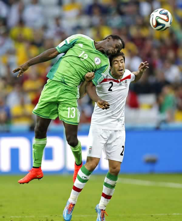 Nigeria&#39;s Juwon Oshaniwa heads the ball past Iran&#39;s Khosro Heydari during the group F World Cup soccer match between Iran and Nigeria. <span class=meta>(AP Photo&#47;Frank Augstein)</span>