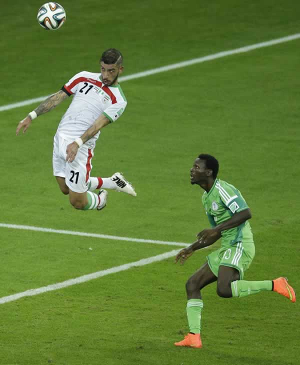 Iran&#39;s Ashkan Dejagah heads a ball as Nigeria&#39;s Juwon Oshaniwa, right, looks on during the group F World Cup soccer match between Iran and Nigeria. <span class=meta>(AP Photo&#47;Michael Sohn)</span>