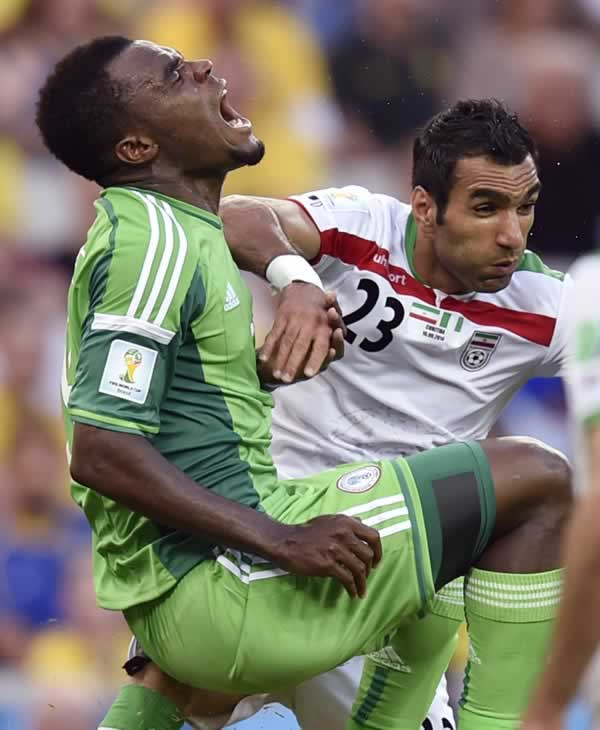 Nigeria&#39;s Emmanuel Emenike, left, grimaces after a challenge from Iran&#39;s Mehrdad Pouladi during the group F World Cup soccer match between Iran and Nigeria. <span class=meta>(AP Photo&#47;Martin Meissner)</span>
