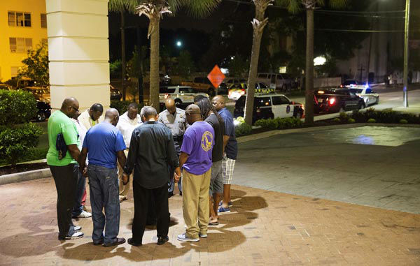 <div class='meta'><div class='origin-logo' data-origin='none'></div><span class='caption-text' data-credit='AP Photo/ David Goldman'>Worshippers gather to pray in a hotel parking lot across the street from the scene of a shooting Wednesday, June 17, 2015, in Charleston, S.C.</span></div>