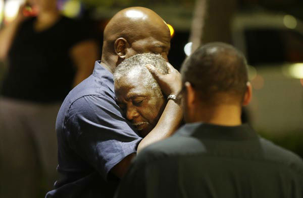 <div class='meta'><div class='origin-logo' data-origin='none'></div><span class='caption-text' data-credit='AP Photo/ David Goldman'>Worshippers embrace following a group prayer across the street from the scene of a shooting Wednesday, June 17, 2015, in Charleston, S.C.</span></div>