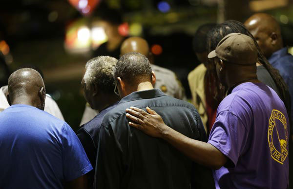 <div class='meta'><div class='origin-logo' data-origin='none'></div><span class='caption-text' data-credit='AP Photo/ David Goldman'>Worshippers gather to pray in a hotel parking lot across the street from the Emanuel AME Church following a shooting Wednesday, June 17, 2015, in Charleston, S.C.</span></div>