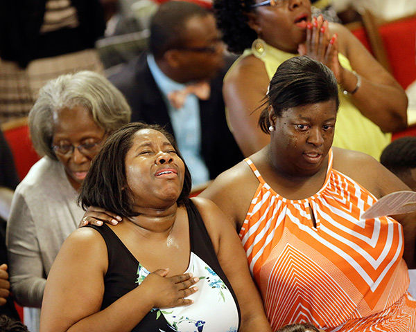 <div class='meta'><div class='origin-logo' data-origin='none'></div><span class='caption-text' data-credit='AP Photo/David Goldman'>Parishioners sing at the Emanuel A.M.E. Church four days after a mass shooting that claimed the lives of its pastor and eight others.</span></div>