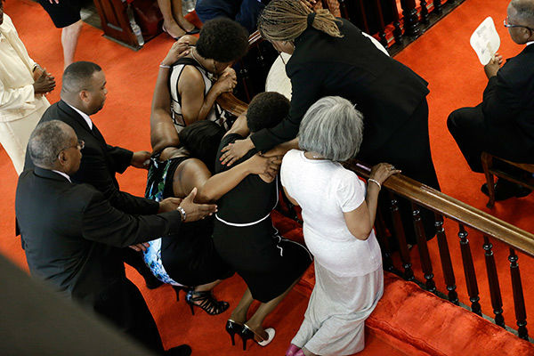 <div class='meta'><div class='origin-logo' data-origin='none'></div><span class='caption-text' data-credit='AP Photo/David Goldman'>Ushers come to the assistance of a woman who collapses as she prays at the Emanuel A.M.E. Church Sunday.</span></div>