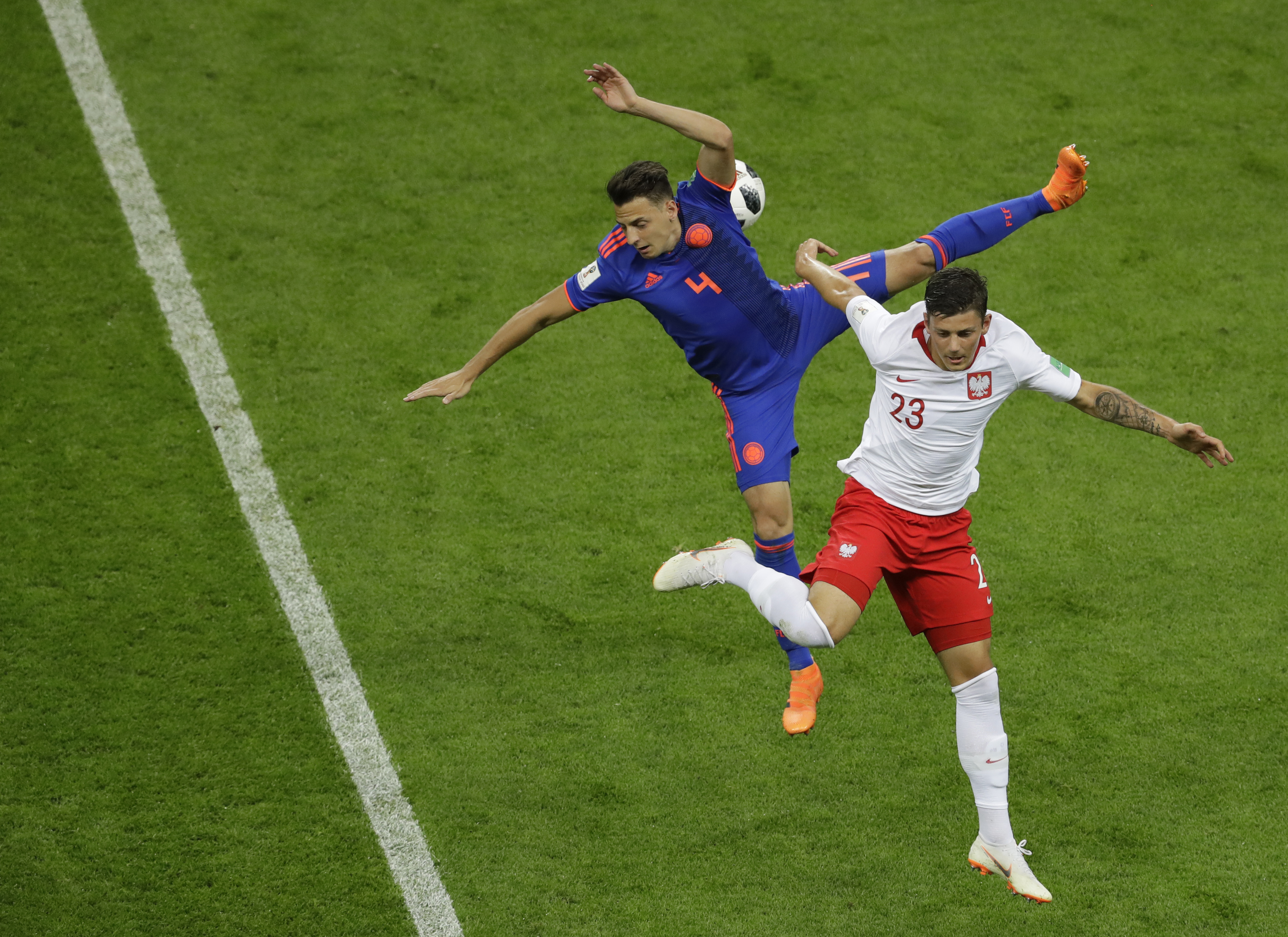 <div class='meta'><div class='origin-logo' data-origin='none'></div><span class='caption-text' data-credit='Sergei Grits/AP Photo'>Colombia's Santiago Arias, left, and Poland's Dawid Kownacki battle for the ball during the group H match at the Kazan Arena in Kazan, Russia, Sunday, June 24, 2018.</span></div>