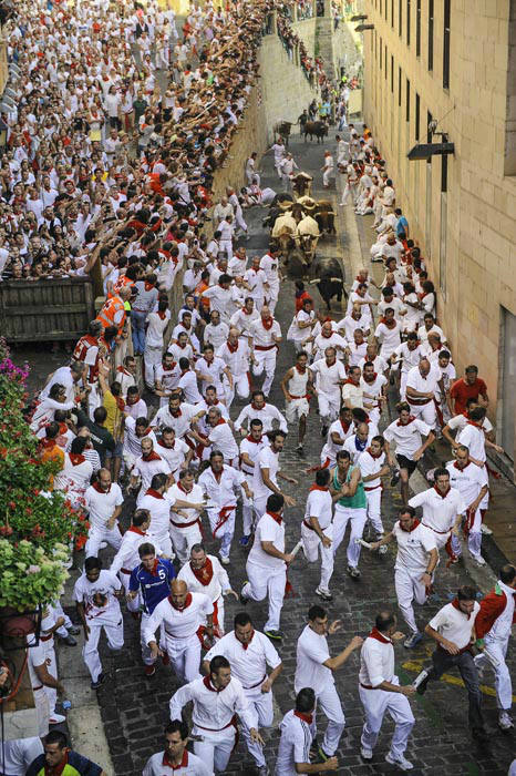 """<div class=""""meta image-caption""""><div class=""""origin-logo origin-image none""""><span>none</span></div><span class=""""caption-text"""">People watch participants run ahead of ''Jandilla'' fighting bulls from Santo Domingo street during the running of the bulls at the San Fermin Festival, in Pamplona, Spain (AP Photo/ Alvaro Barrientos)</span></div>"""