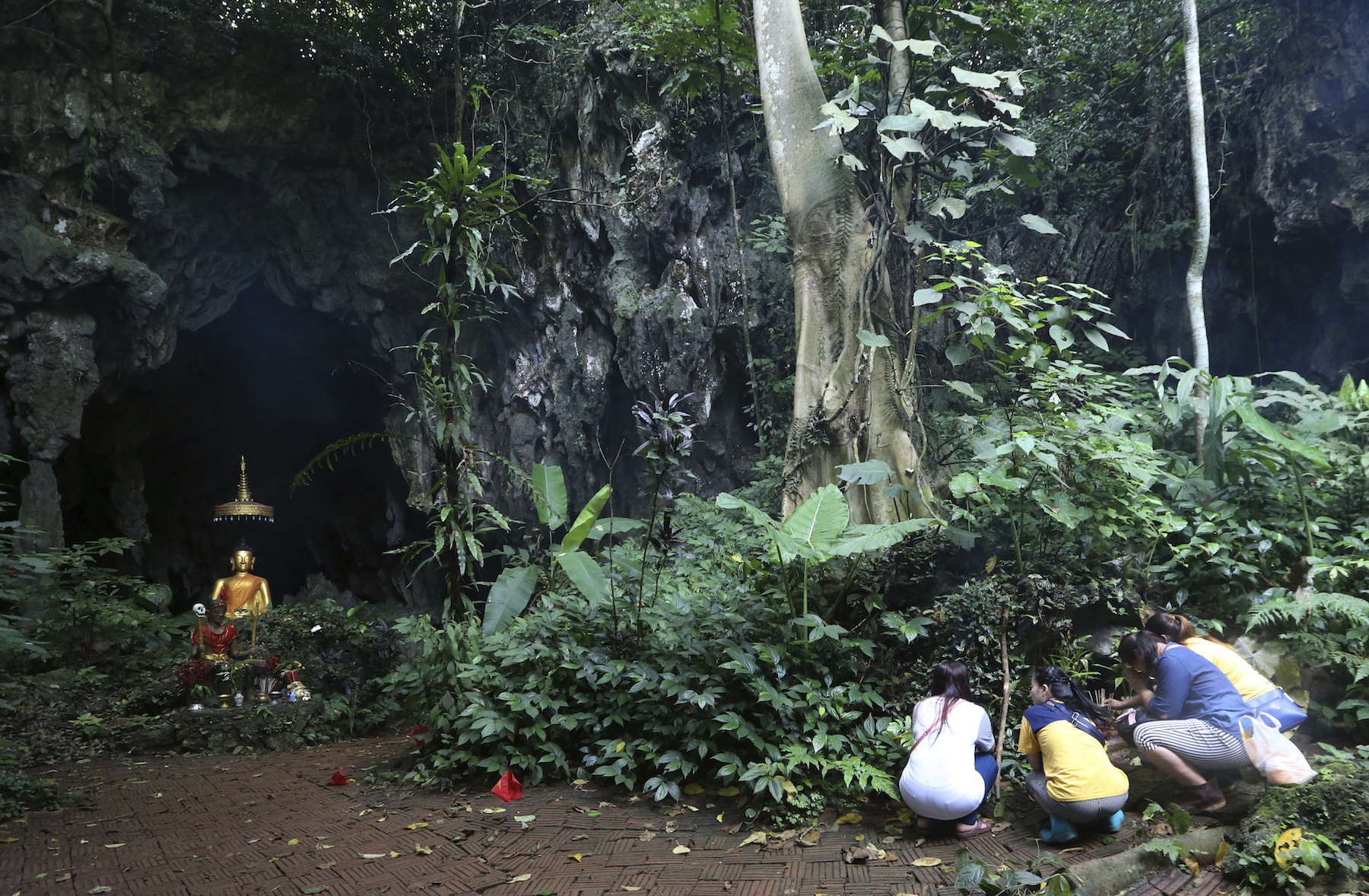 <div class='meta'><div class='origin-logo' data-origin='AP'></div><span class='caption-text' data-credit='AP Photo/Sakchai Lalit'>Family members pray in front giant Buddhist statue near a cave where 12 boys and their soccer coach have been trapped since June 23, in northern Thailand Saturday, July 7, 2018.</span></div>