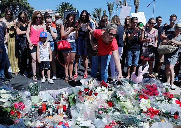 "<div class=""meta image-caption""><div class=""origin-logo origin-image none""><span>none</span></div><span class=""caption-text"">A woman puts flowers near the scene where a truck mowed through revelers in Nice, southern France, Friday, July 15, 2016. (Francois Mori/AP Photo)</span></div>"