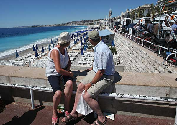 <div class='meta'><div class='origin-logo' data-origin='none'></div><span class='caption-text' data-credit='Luca Bruno/AP Photo'>People sit overlooking the beach and not far from the site of the truck attack in the French resort city of Nice, southern France, Friday, July 15, 2016.</span></div>
