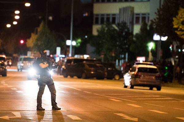 <div class='meta'><div class='origin-logo' data-origin='AP'></div><span class='caption-text' data-credit='AP Photo/Sebastian Widmann'>A masked policeman stands on the street in front of the Olympia mall where a shooting took place in Munich, southern Germany, Friday, July 22, 2016.</span></div>
