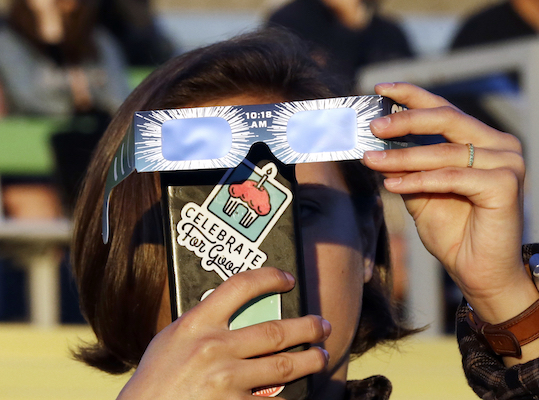 <div class='meta'><div class='origin-logo' data-origin='Creative Content'></div><span class='caption-text' data-credit='AP Photo/Don Ryan'>Catalina Gaitan, from Portland, Ore., tries to shoot a photo of the rising sun through her eclipse glasses at a gathering of eclipse viewers in Salem, Ore., Monday, Aug. 21, 2017.</span></div>