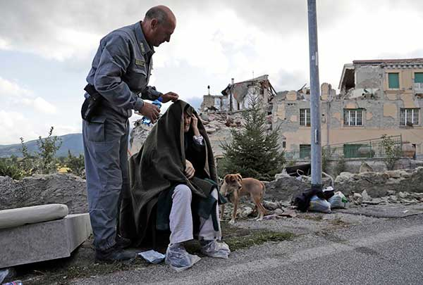 <div class='meta'><div class='origin-logo' data-origin='none'></div><span class='caption-text' data-credit='Alessandra Tarantino/AP Photo'>An elderly man is given assistance as collapsed buildings are seen in the background following an earthquake, in Amatrice, Italy, Wednesday, Aug. 24, 2016.</span></div>
