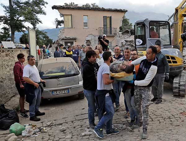 <div class='meta'><div class='origin-logo' data-origin='none'></div><span class='caption-text' data-credit='Alessandra Tarantino/AP Photo'>A man is carried out on a stretcher as a collapsed building is seen in the background following an earthquake, in Amatrice, Italy, Wednesday, Aug. 24, 2016.</span></div>