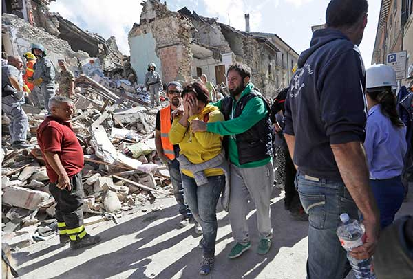 <div class='meta'><div class='origin-logo' data-origin='none'></div><span class='caption-text' data-credit='Alessandra Tarantino/AP Photo'>A woman is comforted as she walks through rubble after an earthquake, in Amatrice, central Italy, Wednesday, Aug. 24, 2016.</span></div>