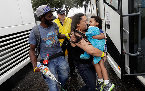 <div class='meta'><div class='origin-logo' data-origin='none'></div><span class='caption-text' data-credit='Eric Gay/AP Photo'>A family is helped to a bus as they are evacuated as the outer bands of Hurricane Harvey begin to make landfall, Friday, Aug. 25, 2017, in Corpus Christi, Texas.</span></div>