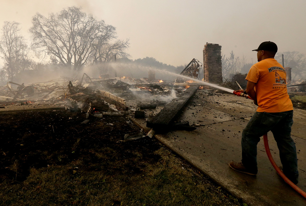 <div class='meta'><div class='origin-logo' data-origin='none'></div><span class='caption-text' data-credit='Jeff Chiu/AP Photo'>A man hoses down hot spots where a house burned down in Santa Rosa, Calif., Monday, Oct. 9, 2017.</span></div>