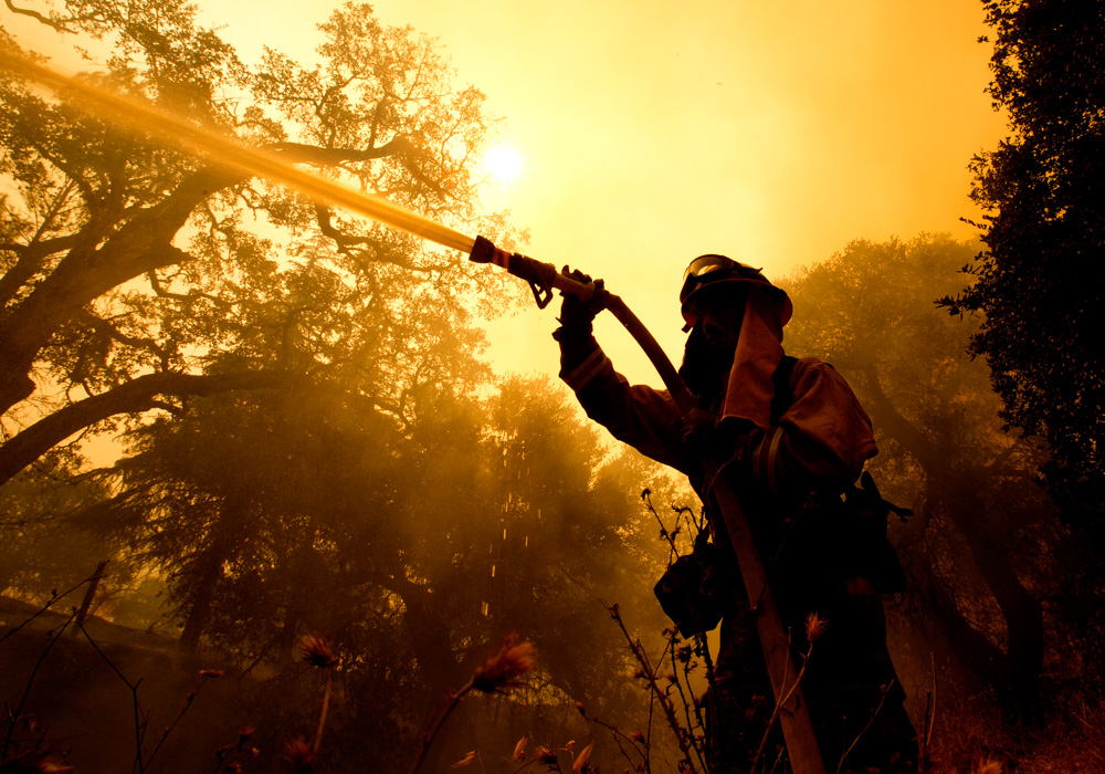 <div class='meta'><div class='origin-logo' data-origin='none'></div><span class='caption-text' data-credit='Rich Pedroncelli/AP Photo'>Napa County firefighter Jason Sheumann sprays water on a home as he battles flames from a wildfire Monday, Oct. 9, 2017, in Napa, Calif.</span></div>