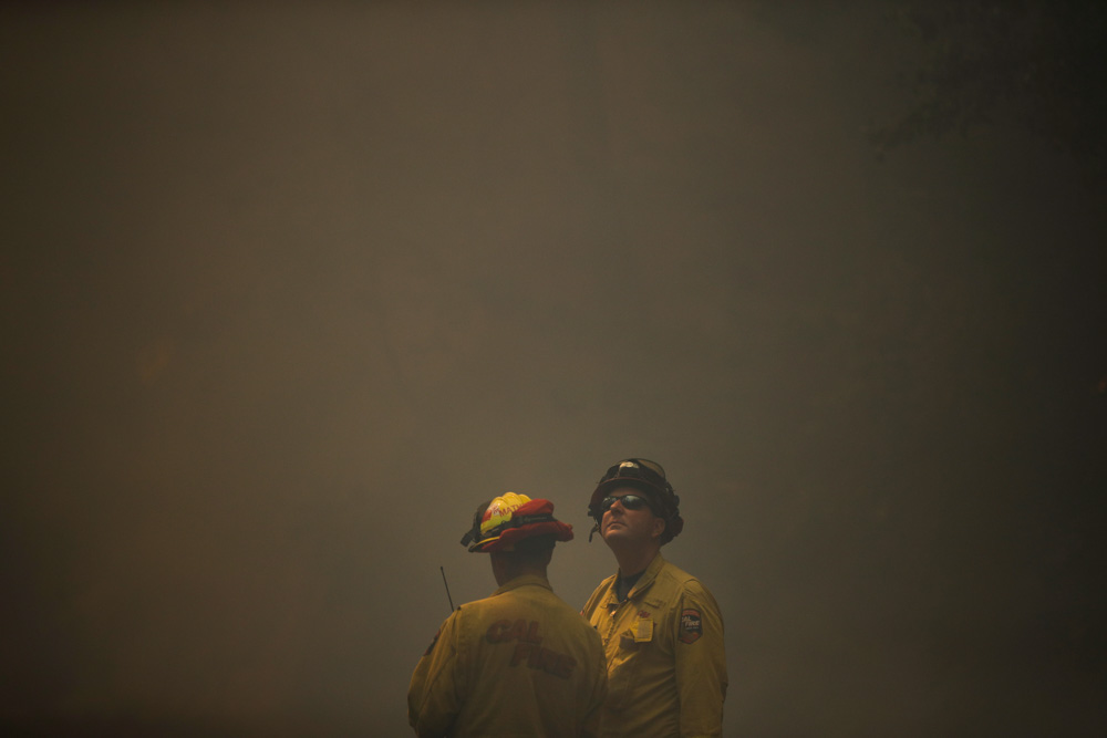 <div class='meta'><div class='origin-logo' data-origin='none'></div><span class='caption-text' data-credit='Jae C. Hong/AP Photo'>Two firefighters look on as think smoke from a wildfire fills the air along the Highway 29 Thursday, Oct. 12, 2017, near Calistoga, Calif.</span></div>