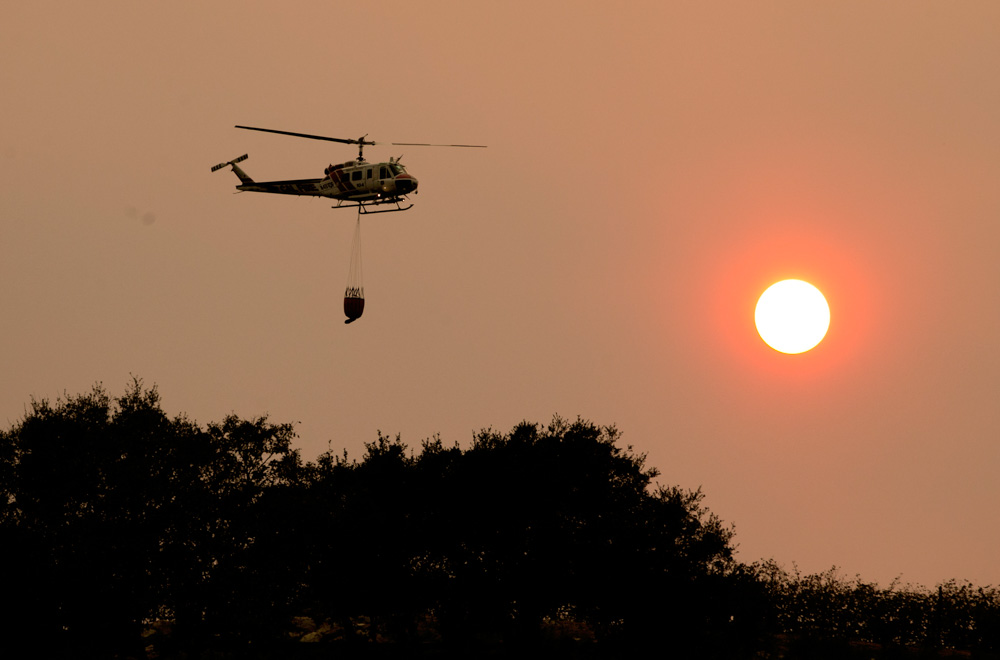 <div class='meta'><div class='origin-logo' data-origin='none'></div><span class='caption-text' data-credit='Rich Pedroncelli/AP Photo'>A helicopter flies through the smokey sky to drop a load of water on a wildfire Thursday, Oct. 12, 2017, in Sonoma, Calif.</span></div>