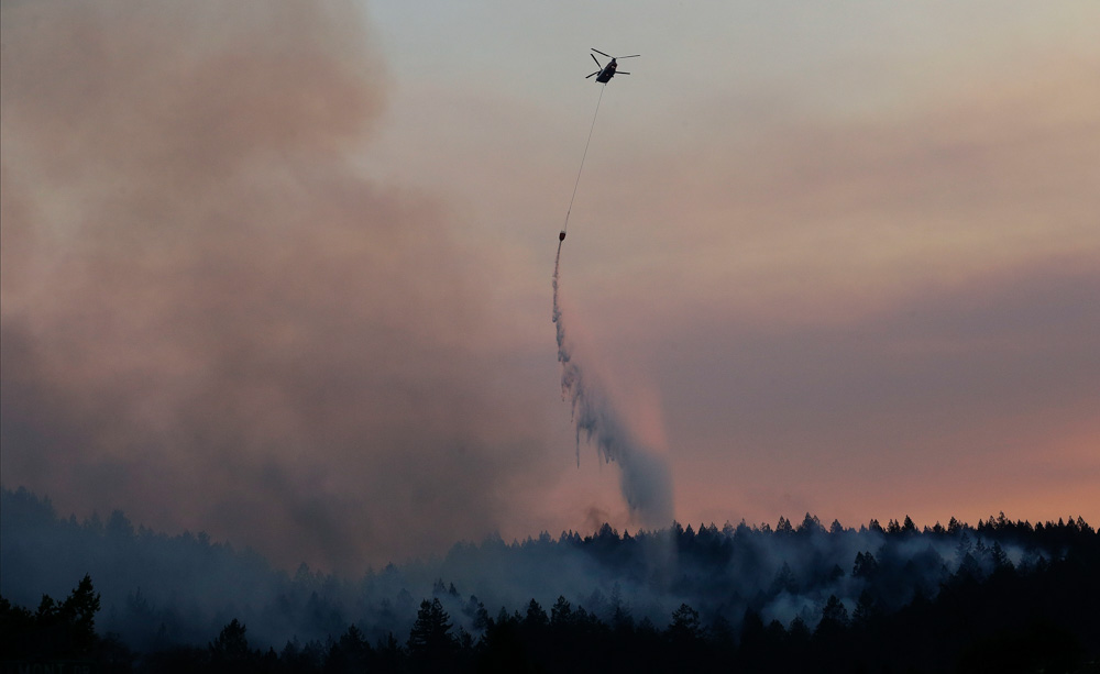 <div class='meta'><div class='origin-logo' data-origin='none'></div><span class='caption-text' data-credit='Jeff Chiu/AP Photo'>A helicopter drops water on a hill in the Oakmont area in Santa Rosa, Calif., Thursday, Oct. 12, 2017.</span></div>