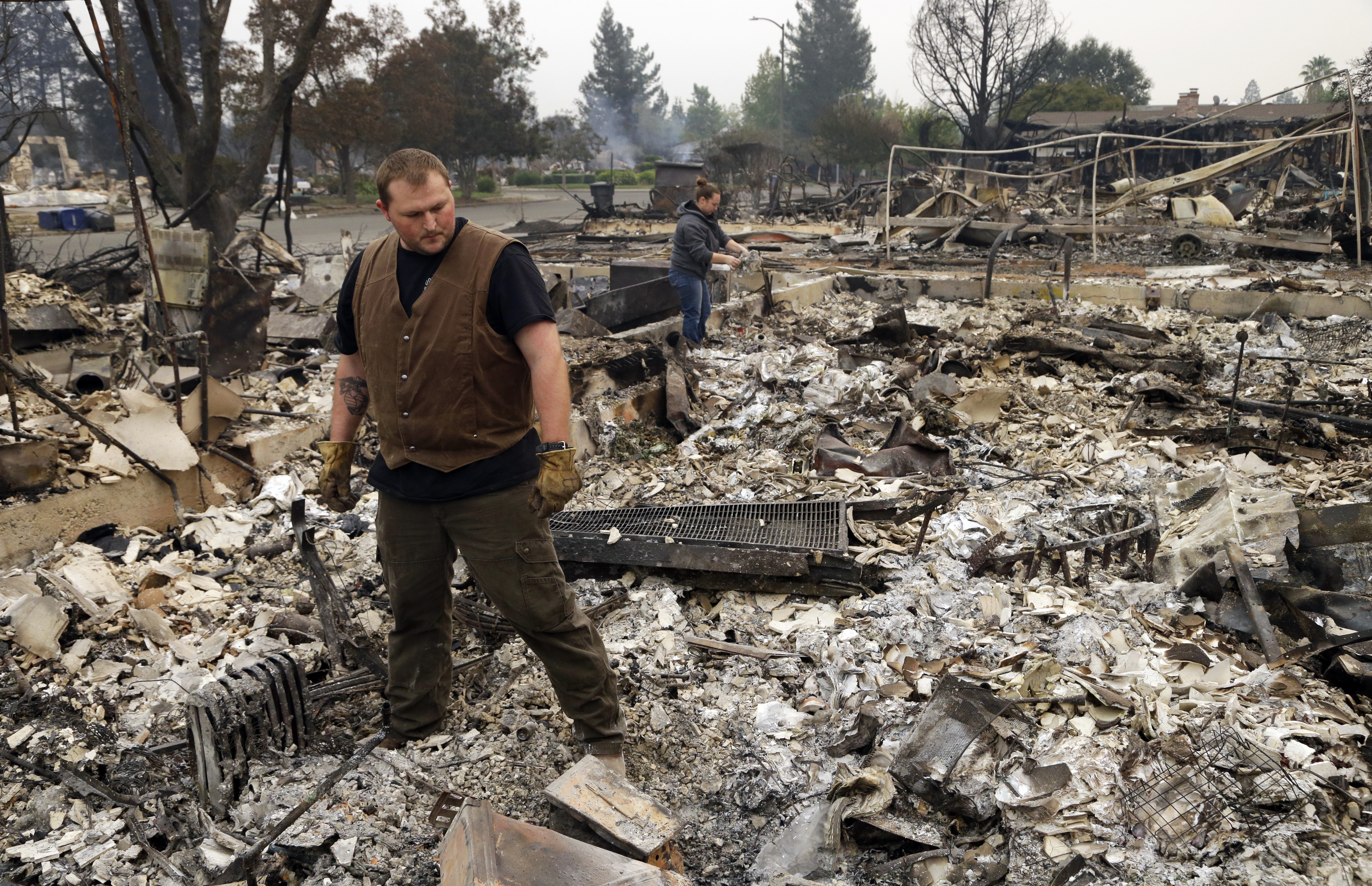 <div class='meta'><div class='origin-logo' data-origin='none'></div><span class='caption-text' data-credit='Ben Margot/AP Photo'>Luke Baier, left, and his wife Gina Baier look through the remains of their home in the Coffey Park area of Santa Rosa, Calif., on Tuesday, Oct. 10, 2017.</span></div>
