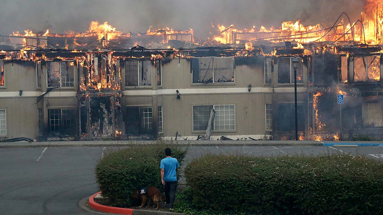 "<div class=""meta image-caption""><div class=""origin-logo origin-image none""><span>none</span></div><span class=""caption-text"">Rudy Habibe and his service dog Maximus walk toward a burning building at the Hilton Sonoma Wine Country hotel, where he was a guest, in Santa Rosa, Calif., Monday, Oct. 9, 2017. (Jeff Chiu/AP Photo)</span></div>"